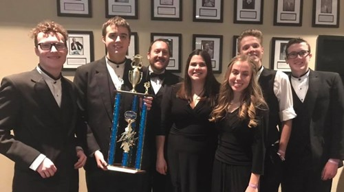 Band director Corey McEnry and several jazz band members show first place trophy.